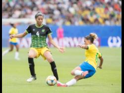 Chantelle Swaby (left) of Jamaica is tackled by Brazil's Tamires Dias De Britto in Jamaica's opening match at the FIFA Women's World Cup 2019 at the Stade des Alpes in Grenoble, France, on Sunday.
