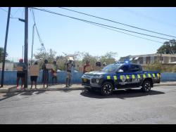 Police personnel keep a close eye on protesters who are against the government's decision to make the  St Joseph's Hospital a quarantine centre.