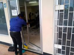 An employee at the passport office in Montego Bay sweeps up broken glass, after a security guard broke through the door, and then drank several substances from a nearby pharmacy.