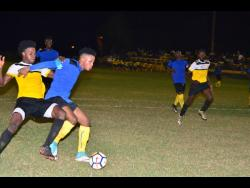 Tevoy Colespring of Meadforest FC holds off Barbican FC's Damian English (left) during their Kingston and St Andrew Football Association/Magnum Super League first-round clash at the Constant Spring Field last season.