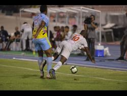 Waterhouse defender Shawn Lawes (left) sends Portmore United striker Javon East tumbling to the ground after a challenge during the Red Stripe Premier League final at the National Stadium on April 29, 2019.