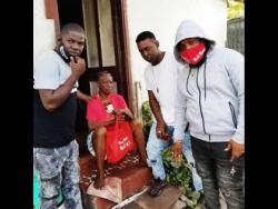 Harry Hype (left), Boom Boom (second right) and artiste Radijah Riskboss (right) hand over a care package to an elderly woman in their give-back drive.