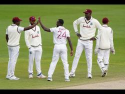 West Indies' Kemar Roach  (centre) celebrates with teammates after the dismissal of England's Jos Buttler during the fourth day of the second Test match at Old Trafford in Manchester, England, on Sunday, July 19.