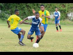File In this file photo from August 2018, Cavalier FC's Javon Smith (centre) slips by Santos FC's Jean-Marc Gayle and drives towards the goal in their Kingston and St Andrew Football Association-sanctioned under-15 final.