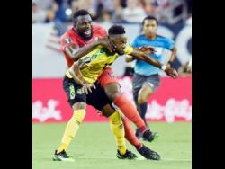 Jamaica's forward Junior Flemmings (foreground) comes under a challenge from United States forward Jozy Altidore during a Concacaf Gold Cup semi-final match in Nashville, Tennessee, on July 3, 2019.