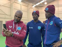 West Indies leg spinner Hayden Walsh Jnr (centre) look over video footage after practice with assistant coach Andre Coley (left) and teammate Nkrumah Bonner in New Zealand.