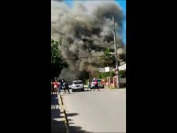 A massive plume of smoke to rises from a residence along Duke Street, Falmouth, Trelawny on Saturday.