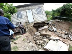 A house teeters on the edge after land slippages threatened the lives and livelihoods of families in Shooters Hill.
