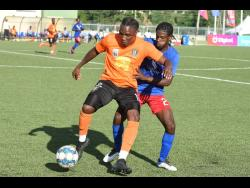 Kemar Flemmings (left) of  Tivoli Gardens FC  shielding the ball from Dunbeholden's Shakeen Powell  during their  Jamaica Premier League match at the UWI/Captain Horace Burrell Centre of Excellence yesterday.  The match ended 1-1.