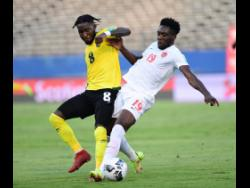 Reggae Boyz defender Oneil Fisher (left) in a battle with Canada's top player Alphonso Davies during yesterday's Concacaf World Cup qualifying match at the National Stadium.