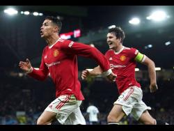 Manchester United's Cristiano Ronaldo celebrates scoring their side's third goal of the game with Harry Maguire during the Champions League Group F soccer match between Manchester United and Atalanta at Old Trafford, Manchester, England, yesterday. United won 3-2.