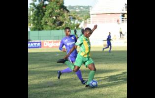 Kingston College's (left) Ronaldo Robinson challenges  Excelsior High's Tariq Duffus (right) for the ball during their ISSA/Digicel Manning Cup match at Montego Bay Sports Complex on  Saturday, September  7.