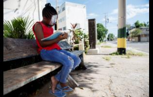 Eight-year-old Shantavia McDonald reads a schoolbook in her community in Kingston. McDonald is left nursing an injured eye following an incident with a schoolmate at the Denham Town Primary School recently.