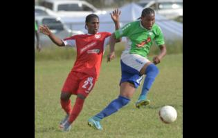Montego Bay United's Keniel Kirlew (right) dribbles away from Boys' Town's Shawn McKoy during their Red Stripe Premier League match at the Barbican field on Wednesday, January 17, 2018.