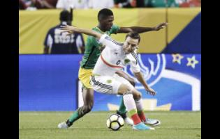 National defender Damion Lowe (left) battles Mexico's Erick Torres during a Concacaf Gold Cup match in Denver, Colorado, on Thursday, July 13, 2017. The game ended in a 0-0 draw.