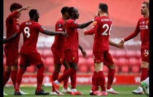 Liverpool's Sadio Mane (centre) celebrates after scoring the opening goal during the English Premier League match between Liverpool and Aston Villa at Anfield Stadium in Liverpool, England, Sunday, July 5, 2020.