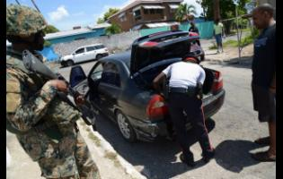 Members of the security forces conduct a search along Greenwich Road in St Andrew  where a State of Emergency was declared in 2018.