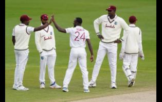 West Indies' Kemar Roach (center) celebrates with teammates after the dismissal of England's Jos Buttler during the fourth day of the second cricket Test match between England and West Indies at Old Trafford in Manchester, England,  July 19, 2020.