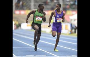 Calabar High School's Tyreke Wilson (left) shares a laugh with Jhevaughn Matherson of Kingston College during the preliminary round of the Class One boys' 100m at the ISSA/GraceKenedy Boys and Girls' Athletics Championships on March 23, 2018.