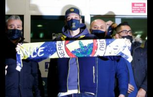 Mesut Ozil, a former Germany midfielder, poses for the photographers with a Fenerbahce scarf after arriving at the Ataturk Airport in Istanbul on Monday, January 18.