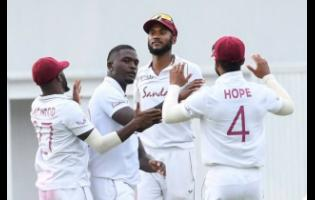 Jayden Seales, (second left), is congratulated by teammates after taking a South African wicket in the first Test.