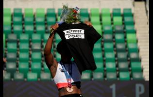 In this June 26, 2021 file photo, Gwendolyn Berry displays her Activist Athlete T-shirt over her head during the medal ceremony after the finals of the women's hammer throw at the US Olympic track and field trials in Eugene, Oregon.