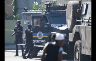 Members of the security forces carry out an operation along Mountain View Avenue in Kingston, following a murder in the area.