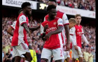 Arsenal's Bukayo Saka (centre) celebrates after scoring his side's third goal during the English Premier League  match between Arsenal and Tottenham Hotspur at the Emirates stadium in London yesterday. Arsenal won 3-1.