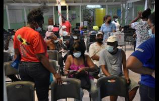 Persons waiting at the Spanish Town Health Centre on Sunday waiting to get vaccinated.