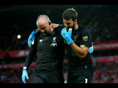 Liverpool goalkeeper Alisson Becker (right) reacts as he leaves the pitch after an injury during the English Premier League match between Liverpool and Norwich City at Anfield in Liverpool last Friday.