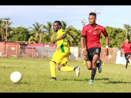 Renoir Elliott (left) of Vere FC challenges Downs FC's Romario Witter for the ball during their JFF All-Island Confederation Play-Offs encounter at the Wembley Centre of Excellence in Hayes, Clarendon, on Sunday, June 3.