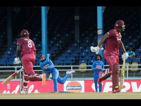 India's captain Virat Kohli (behind left) throws the return on an attempt to run out West Indies' batsman Sheldon Cottrell (right) as captain Jason Holder (left) scores a run during their second one-day international cricket match in Port of Spain, Trinidad, last Sunday.