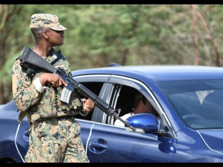 A member of the Jamaica Defence Force mans a state of public emergency checkpoint.