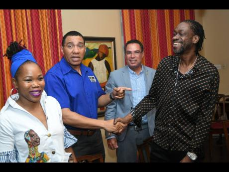 Bounty Killer, the poor people governor, shakes hands with Prime Minister Andrew Holness following a meeting held with entertainers at Vale Royal recently. Looking on is Queen Ifrica (left) and Daryl Vaz.