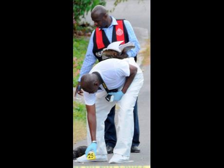 Detectives process a crime scene on Commission Road in Rockfort, east Kingston.