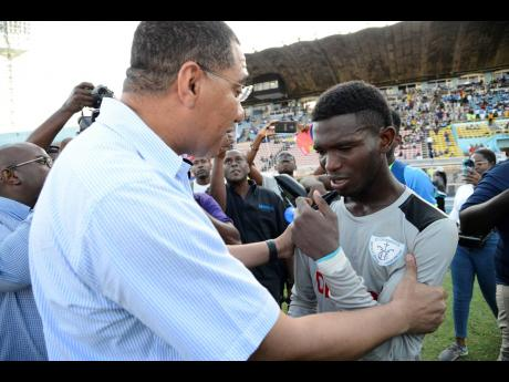 Prime Minister Andrew Holness congratulates St Catherine High School goalkeeper, Raheem Henry, after the St John's Road-based school beat Excelsior High School 3-2 in the Walker Cup final last Friday, November 29, 2019.