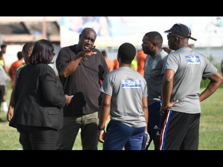Members of the coaching staffs of RSPL outfits Tivoli Gardens and Waterhouse speak with match commissioner Elaine Walker-Brown  at the Edward Seaga Sports Complex yesterday.