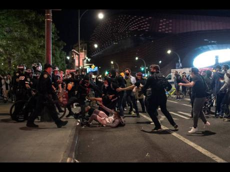 Police move to detain protesters as they march down a street during a solidarity rally for George Floyd in the Brooklyn borough of New York City on Sunday.