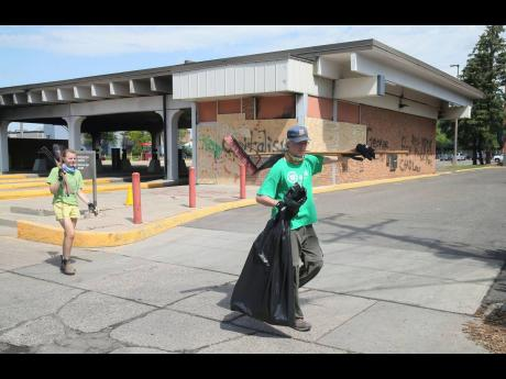 Clean-up volunteers walk past the damaged Wells Fargo Bank in Minneapolis, Minnesota, yesterday.