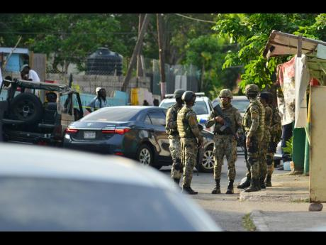 Soldiers in August Town last Wednesday where 44-year-old Susan Bogle was killed.