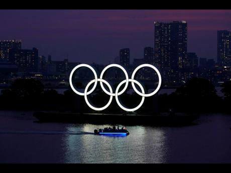 The Olympic rings float in the water at sunset in the Odaiba section of Tokyo, Japan, on Wednesday.