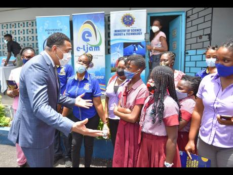 Prime Minister Andrew Holness  speaks with students and teachers at Balcombe Drive Primary School in St Andrew last Thursday, after handing over tablets to  teachers at the institution.