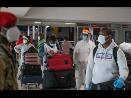 Returning Jamaicans enter the arrival hall at the Norman Manley International Airport in May.