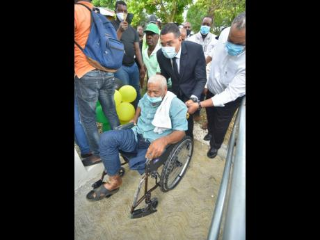 Prime Minister Andrew Holness (centre) pushes the wheelchair with  Winston Wint up the ramp leading into his one-bedroom house, which was handed over in Bogue district, St Elizabeth, on July 17. To the prime minister's left is National Director of the New Social Housing Programme Danville Walker.