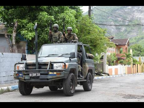 Soldiers patrol August Town after the community was designated a zone of special operations.