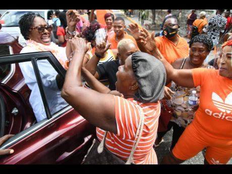 Supporters of the People's National Party greet South West St Andrew Member of Parliament, Dr Angela Brown Burke, outside of Gordon House yesterday.