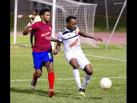 File Dunbeholden's Adrian Williams (left)  challenges  Cavalier's Nicholas Hamilton  in a  Red Stripe Premier League encounter at Stadium East on Sunday, December 16, 2018.