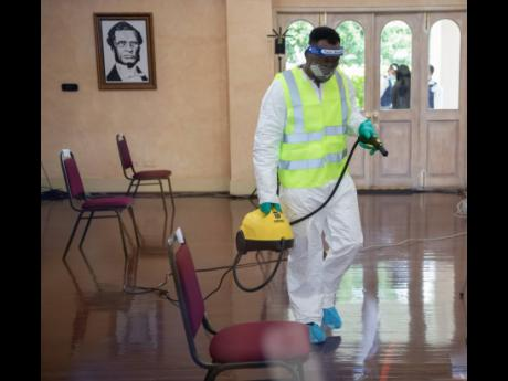 Cleaning staff sanitise the King's House banquet hall ahead of the swearing-in ceremony for Prime Minister Andrew Holness on September 7.