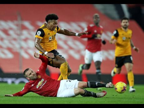 Manchester United's Luke Shaw challenges Wolverhampton Wanderers' Adama Traore during the English Premier League match between Manchester Utd and Wolverhampton Wanderers at Old Trafford stadium in Manchester, England, yesterday.