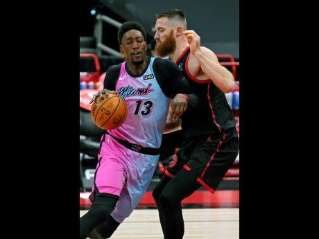 Miami Heat centre Bam Adebayo (13) crashes into Toronto Raptors centre Aron Baynes (46) during the first half of an NBA basketball game Wednesday, January 20, 2021, in Tampa, Florida.